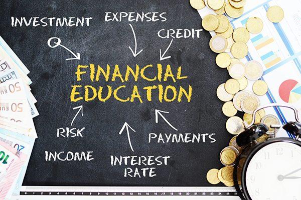 Financial education concept handwritten on blackboard, near cash